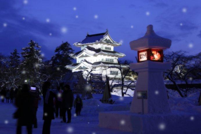 雪の中でライトアップされる弘前城。