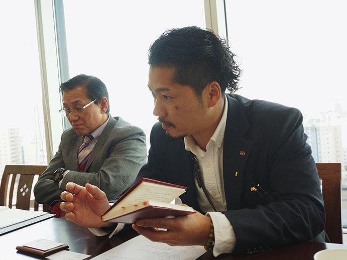 上山さんが手に持っているのがグループの理念が込められた「赤本」です