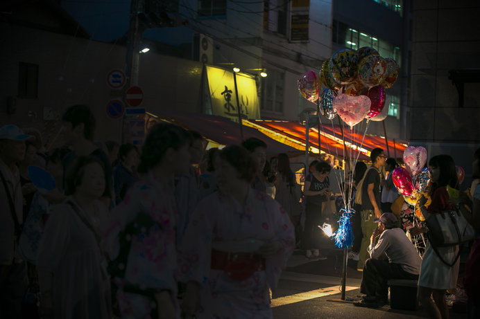 風船屋のライトがお祭り雑踏を印象的に見せる