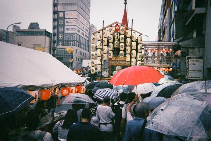 人ごみを避けて雨の中進む時に、ヒョイと傘をあげて進む瞬間、赤い傘が祇園祭のアクセントに