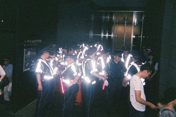 祇園祭の警備員のベストがカメラのフラッシュでまぶしく反射する、日常の風景が非日常化する瞬間