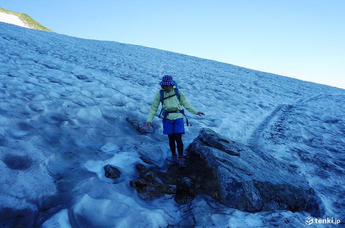 早朝、万年雪が形成する雪渓を歩く