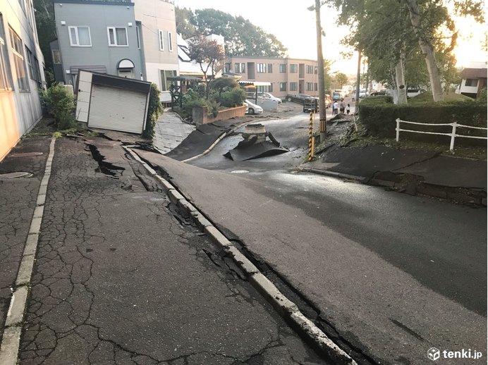 地盤沈下で道路や住宅が傾いているようす