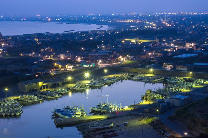 漁港の眩い光と、奥に広がるほの明るい町灯りのコントラストも味わい深い