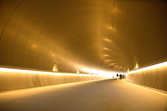 美術館へと続くスタイリッシュなトンネルは、先が見えないよう緩やかなカーブを描き、来場者の期待感を高める