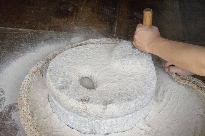 石臼で小麦を碾く