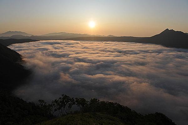 霧に覆われた朝焼けの摩周湖。湖面はまったく見えない。
