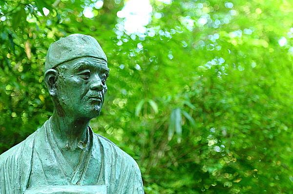 中尊寺の芭蕉像。新緑の中、句碑とともに佇んでいる。